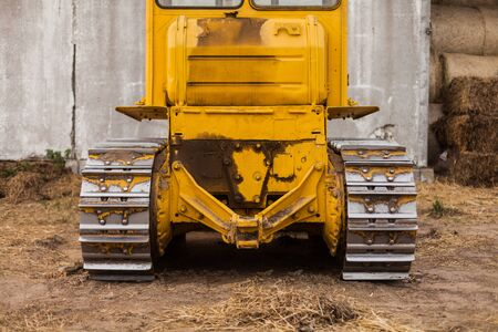 Close-up of crawler bulldozer truck. Earthmoving heavy machinery. Yellow crawler machinery. Yellow Tractor on caterpillar tracks, tractor tracks Stock Photo