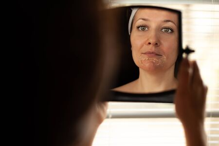 The girl with problem skin looks in the mirror. Stock Photo