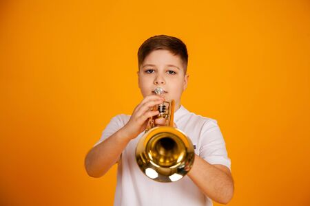 A boy plays the trumpet. A handsome teenager boy in a white T-shirt plays trumpet musical instrument Standard-Bild