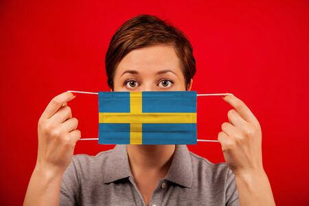 Coronavirus COVID-19 in Sweden. Woman in medical protective mask with the image of the flag of Sweden. The concept of preventing the spread of the epidemic and treating coronavirus. Stockfoto
