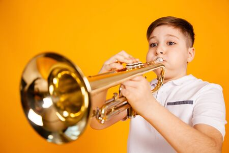 A cheerful boy plays the pipe blowing his cheeks. Humor playing a wind instrument.