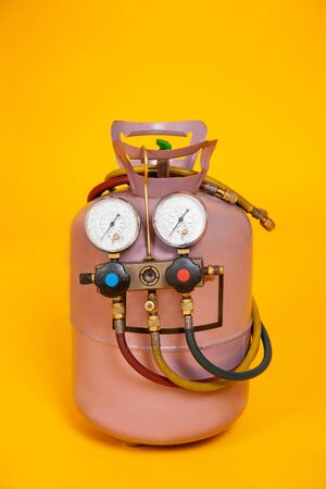 Pressure gauges measuring devices for refueling air conditioners, sensors. Cylinder with freon on a yellow background. Tools for HVAC.