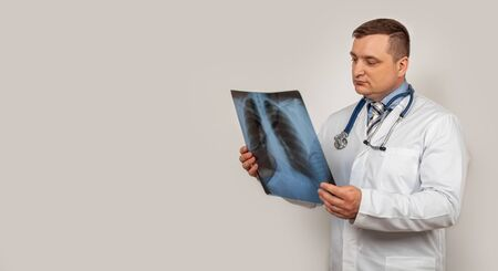 A male doctor looks and studies an x-ray of the chest. A snapshot of a person s lungs with signs of pneumonia.