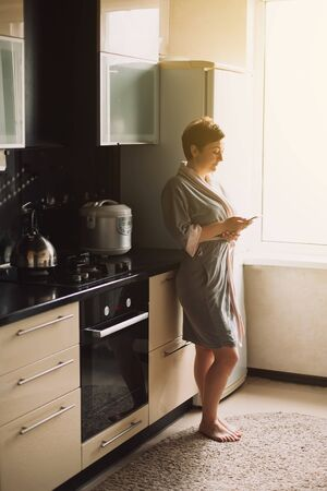 Work from home. Pretty woman in a bathrobe in the kitchen in the morning communications and works on the phone at home. Working at home