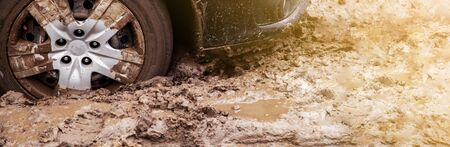 The car got stuck on a dirt road in the mud. Wheel of a car stuck in the mud on the road. Car on a dirt road. Outdoor, adventure and travel