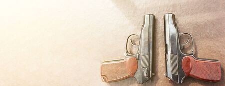 The gun lies on a table on old village boards, legalization of weapons. Crime problems. Weapons for sports and self-defense. Conceptual of violence, homicide, crime and burglary. Copyspace