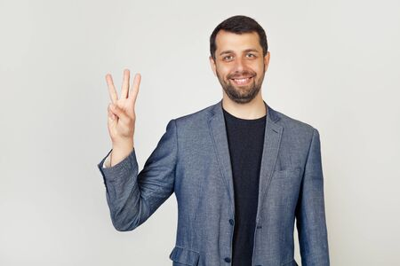 Young male businessman with beard smiling showing fingers number three