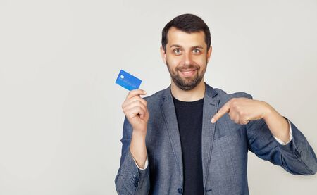 Young businessman man with beard bank customer holding a credit card