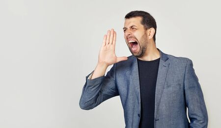 A young man with a beard screams out loud with his hand near his mouth.