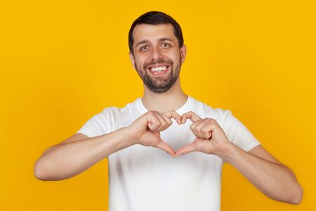 Handsome young man, smiles and makes a heart-shaped symbol with his finger