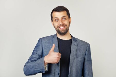 Young man with bristle businessman showing finger up to camera with happy smile Stock fotó