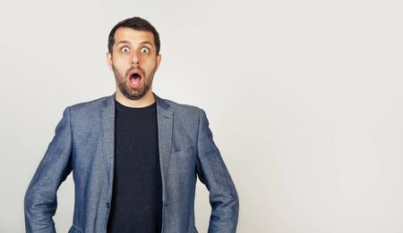 A man with a beard opened his mouth, scared and shocked by an expression