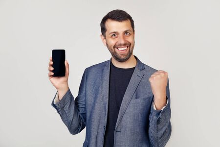 Young man showing smartphone screen screaming proud and celebrating success 5G