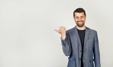 The young man with a beard, looking and pointing to the side with a thumb at a place for advertising Stock fotó