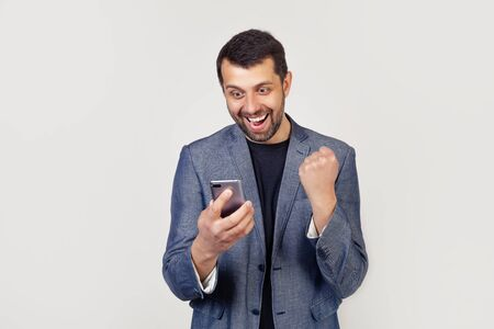 Happy business man holding a smartphone and celebrating his success Stock fotó