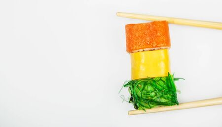 Sushi roll with chopsticks, with cucumber kappa maki roll. Japanese kitchen. Various sushi and rolls with fish cheese and with chuka salad in chopsticks isolated on a white background Foto de archivo