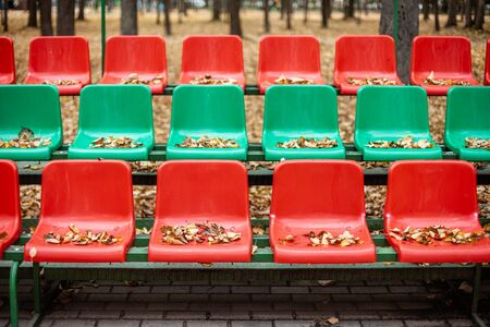Empty sports stands with red and green seats on an autumn day.