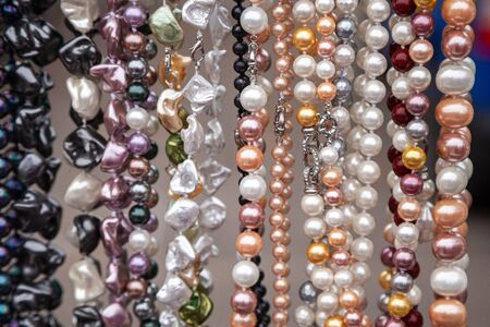 Various colorful beads in the market. Wallpaper background of a colorful necklace made of precious stones and colored beads. Semi-precious jewelry.