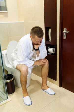 Depressed young man in a white bathrobe sitting on the toilet in the bathroom with his head in his hands while sitting on the toilet. Personal morning routine. Hygiene in the morning concept.