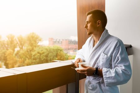 A young man in a white coat on the balcony with a cup of coffee. Morning coffee or tea is holding a cup of man on the summer terrace