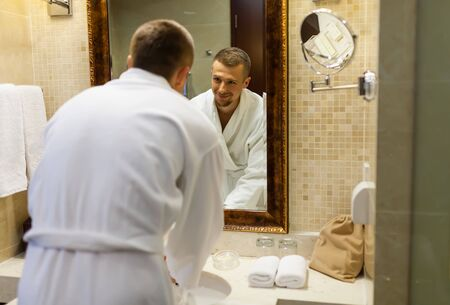 The guy smiles in a white coat and looks at himself in the bathroom mirror in the morning. Starting a new day with a smile. Handsome young man standing in front of a mirror