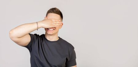 Portrait of a charming young man, an excited European guy, covering his eyes with his palm and smiling, waiting for an unexpected gift, waiting for a gift, counting ten, playing hide and seek