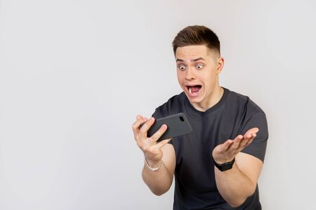 A surprised, shocked young man holds a smartphone in his hands and looks at the display with his mouth open and big eyes. A guy with a sagging jaw in fear came out first in the game, became a champion