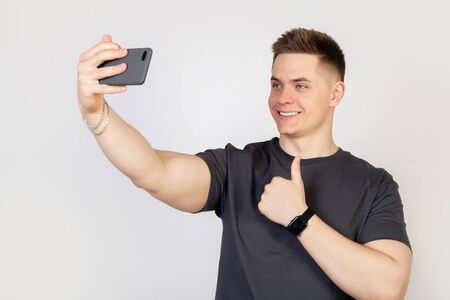 Portrait of a stylish handsome smiling young man taking a selfie on a smartphone, holding a mobile phone in his outstretched hand and trying to look beautiful in photo white background Online concept