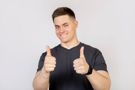 A young man in a gray T-shirt on a white background, showing a finger up to the camera with a happy smile. All is well, shows success.