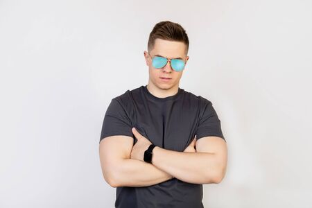 Athletic guy in sunglasses. The young man in sunglasses, frowning in displeasure, holds his hands clasped.