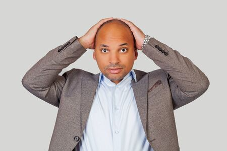 African american attractive guy holding head with hands having an awkward expression looking at his best friend who doing something stupid in public.