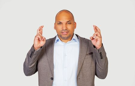 Handsome African-American young guy crosses his fingers with a worried expression, asking God please cross his fingers with a pitiful look hoping that the boss did not notice that he was late for work