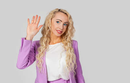 A woman raises her hand in a hello greeting, waves to you with a raised hand.