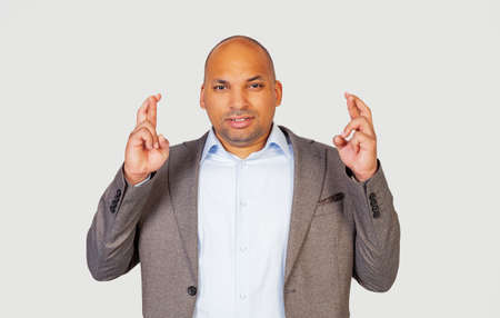 African-American young guy crosses his fingers with a worried expression, asking God, please cross his fingers with Stock fotó