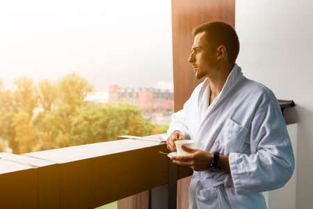 Young man in a white coat on the balcony with a cup of coffee Stock fotó
