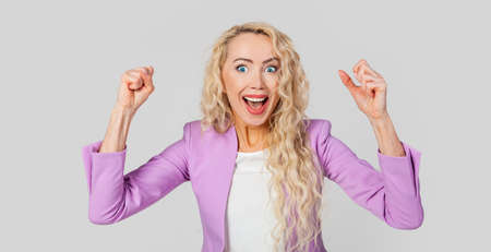 Cheerful, happy woman raising her hands with her fist, cheering for the team, winning a huge bet, playing in the casino in delight Stockfoto