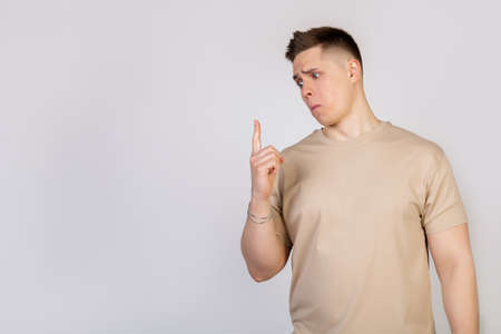 A handsome guy with a beautiful haircut looks at the camera with a funny facial expression, holding his lips and pointing his finger up. Copy space