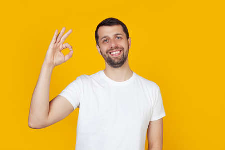 Young man with a beard in a white t-shirt happy face, smiling positively, makes okay sign with hand and fingers. It's okay. Lucky expression. Stands on isolated yellow background.