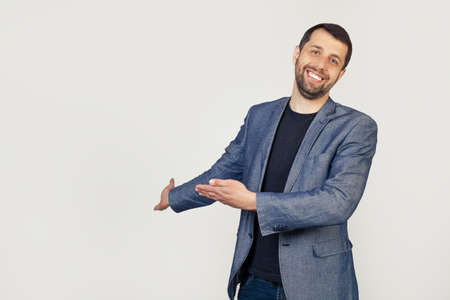Young businessman man with a beard in a jacket, inviting to enter, smiling naturally with an open hand. Portrait of a man on a gray background.