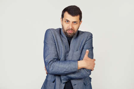 Young businessman man with a beard in a jacket, shaking and freezing from the winter cold with a sad and shocked expression on his face. Portrait of a man on a gray background.
