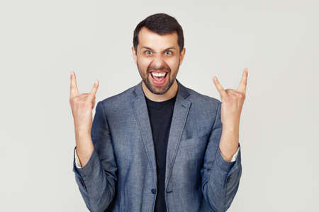 Young businessman man with a beard in a jacket, shouting with a crazy expression on his face, making a rock symbol with his hands up. Music star. Heavy music concept. man on a gray background.