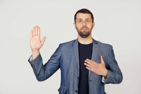 Young businessman man with a beard in a jacket, swears, putting his hand on his chest and open palm, making an oath of promise of loyalty. Portrait of a man on a gray background. Archivio Fotografico