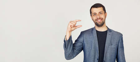 Young businessman man with a beard in a jacket, smiling and confidently gesturing with his hand, making a small size sign with fingers looking and the camera. Measurement concept. gray background.