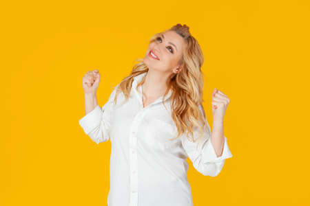 Excited happy European blonde woman wearing white shirt, enthusiastically shouts yes, chants and triumphs, becomes champion, wins the competition. Standing against yellow background Фото со стока