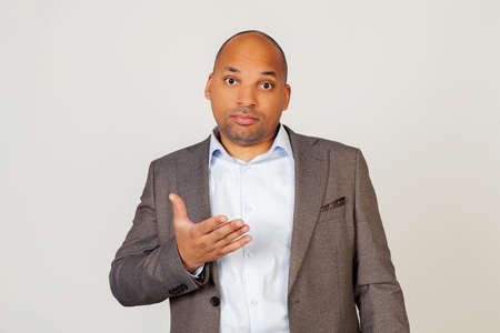 Young african american guy businessman looking at the camera with a surprised facial expression and gesturing with his hand. Standing on a gray background