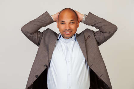 Portrait of an upset young African American guy businessman looking at the camera holding hands in his head. Standing on a gray background