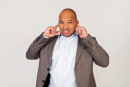 Portrait of unhappy young african american guy businessman covering ears with fingers with annoyed facial expression trying not to hear bad singing and no pleasant sound. Standing on a gray background