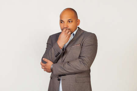 Portrait of an unhappy young African American guy businessman, looks tense and nervous with his hands on his mouth biting his nails. Anxiety problem. Standing on a gray background