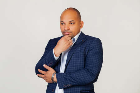 Portrait of an unhappy young African American guy businessman, thinking looking tired and bored with depression problems with crossed arms. Standing on a gray background
