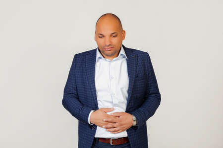 Portrait of a sick young African American businessman guy, with a hand on his stomach due to indigestion, feeling sick. Pain concept. Standing on a gray background